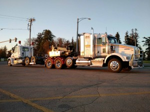 Photo of a semi truck hauling an additional heavy duty tractor trailer.