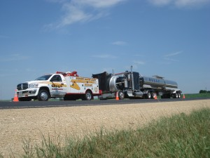 Photo of a Guy's Towing and Service tow truck relieving a stranded customer with roadside assistance.