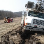 Photo of Alliant Energy truck stuck in the mud awaiting Guy's Towing and Service.