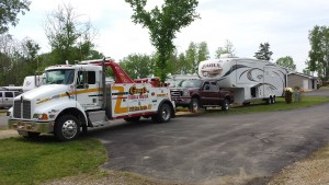 Photo of a trailer hauling a medium duty truck and motor home to the desired location.