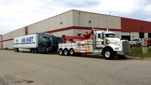 Photo of a trailer hauling a heavy duty tractor-trailer to the desired location.