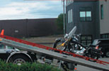 Photo of a motorcyle being loaded onto a trailer to be towed.