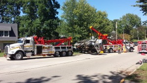 Photo of a heavy duty tow truck receiving and towing a tractor trailer on the side of the road.